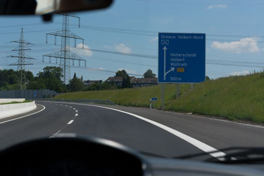 German motorway sign with inscription in German Driving direction to the cities - Velbert, Heiligenhaus, Wuelfrath and Hetterscheidt