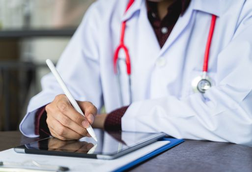 Close up shot hand of Doctors with stethoscope are using tablets to write treatment reports or view patient information. New normal of medical use remote technology for follow up and consult patients