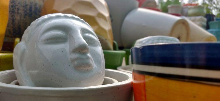 Buddha face as a garden porcelain pot in a nursery