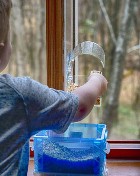 Small boy loads window-mounted bird feeder with seed.