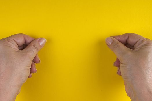 Hands with clenched fingers in a pinch on a yellow background