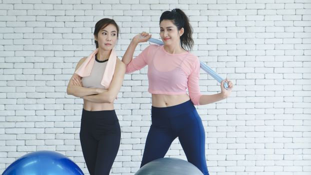 A group of young Asian women wearing sportswear is talking about sports in the gym after exercising by doing stretching with yoga postures.