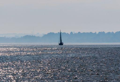Sailboat on water against hazy shoreline