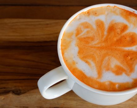 art leaves on hot tea with milk in cafe