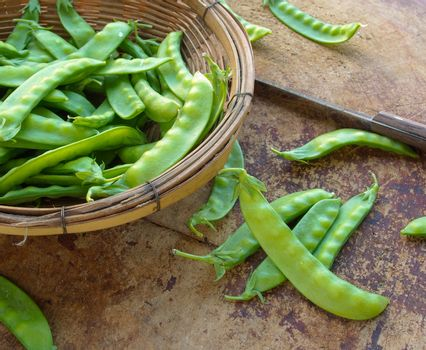 Peas on wooden cutting board to prepare the food.