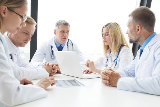 Team of experts doctors examining mri report on hospital office meeting