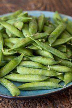 raw peas on dark wood