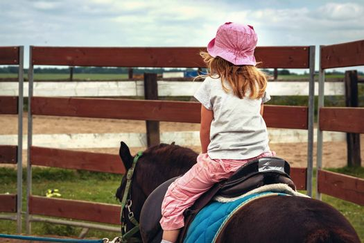 Pony riding, young girl as a horseback jockey rear view. female child as a horse rider. equestrian ride lesson for little kids. back view of sport and recreation with equine or stallion. Active hobby.