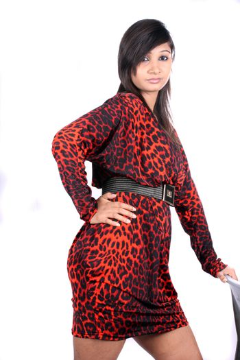 A beautiful Indian woman in a red spotted dress, on white studio background.