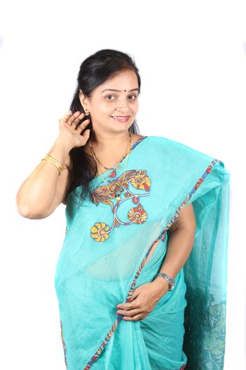 A beautiful middle aged Indian woman in saree showing her earring, on white studio background.