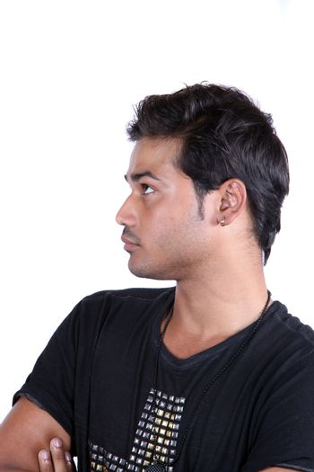 A portrait of a young Indian guy lost in thoughts, on white studio background.