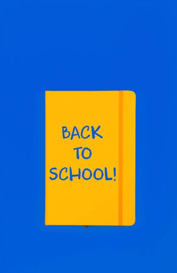 Back to school handwritten sign on yellow leather cover notebook over blue paper background with copy space