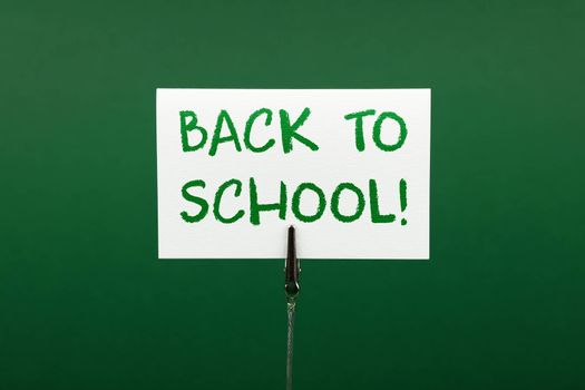 Back to school white crayon handwritten sign over green paper background with copy space