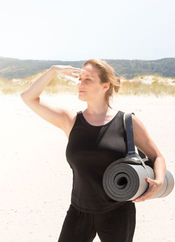 Woman in sportswear with a rolled-up mat under her arm at the beach, and protecting herself from the sun with one hand to look away