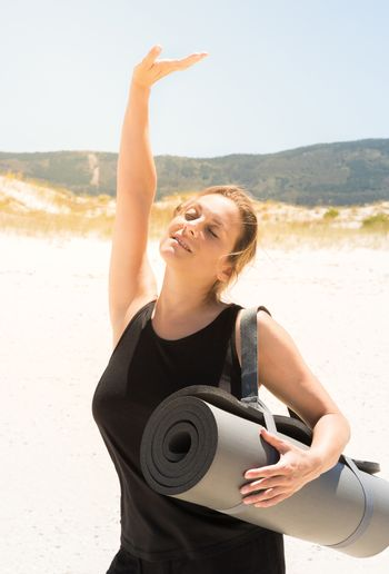 Woman stretching out in sportswear with a rolled-up mat under her arm at the beach