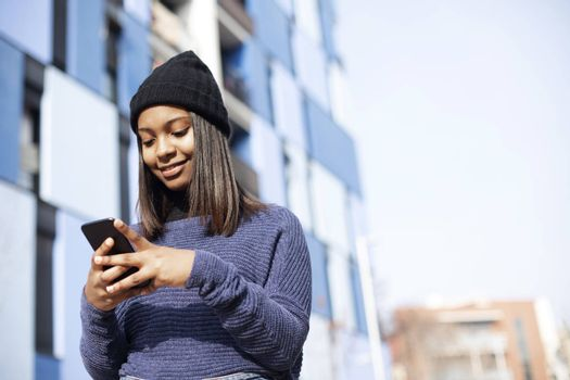 Portrait of African American young woman wearing a wool cap standing on the street while using a mobile phone