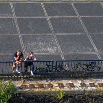 Amsterdam, the Netherlands — July 28, 2019. A photo looking down at a man and a woman leaning on a fence near a pier peering into the distance.