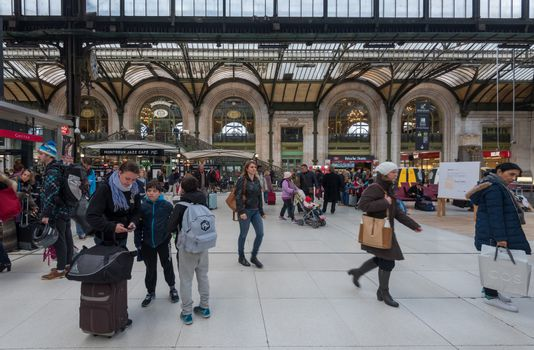 Paris, France -- November 4, 2017 -- Mother with 2 young boys checks her mobile phone in the bustling Gare de Lyon train station in Paris.