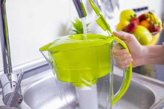 Woman filling water filter jug in the kitchen. Purification and softening of drinking tap water. Closeup