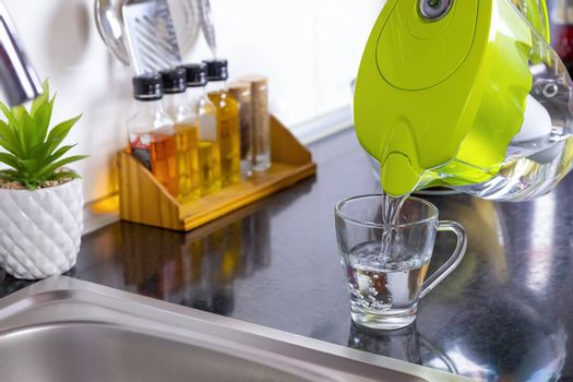 Pouring filtered water into glass from water filter jug in the kitchen. Purification and softening of drinking tap water. Closeup. Focus on glass.