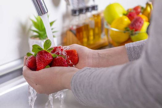 Woman hands washing strawberries in the kitchen. Eating fresh and healthy fruits concept. Closeup