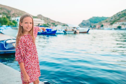 Adorable little girl in port at summer day