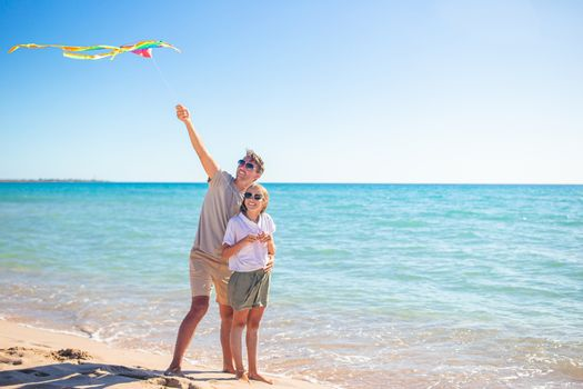 Family playing with a kite on the beach