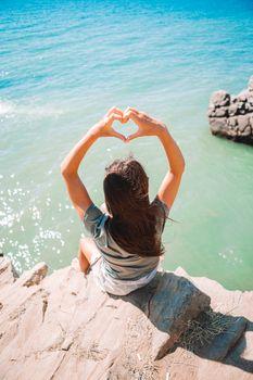 Tourist woman outdoor on edge of cliff seashore