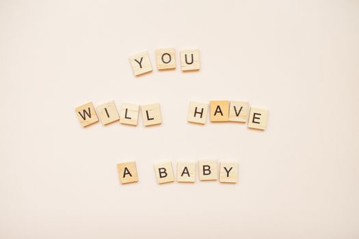 """The inscription """"you will have a baby"""" made of wooden blocks on a light pink background."""