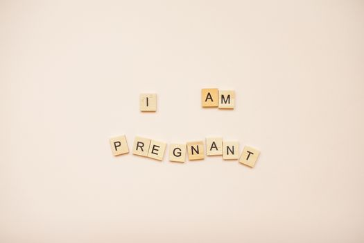 """The inscription """"I am pregnant"""" made of wooden blocks on a light pink background."""
