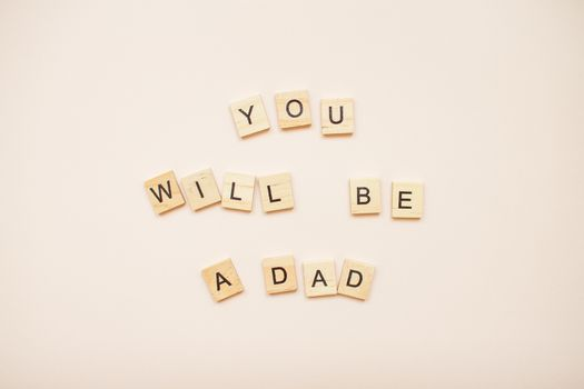 """The inscription """"you will be a dad"""" made of wooden blocks on a light pink background."""