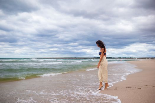 Young woman on the beach in the storm