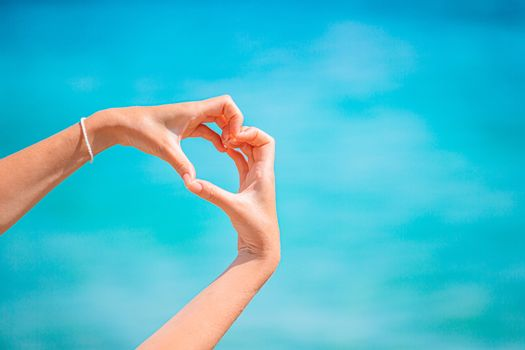 Female hands in the form of heart against the turquoise sea