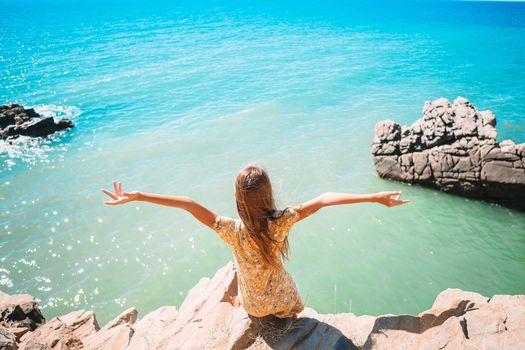 Little girl outdoor on edge of cliff seashore