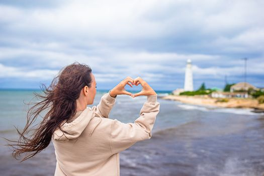 Woman walk to the lighthouse and make heart