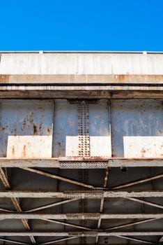 Edge of bridge truss underside against blue sky