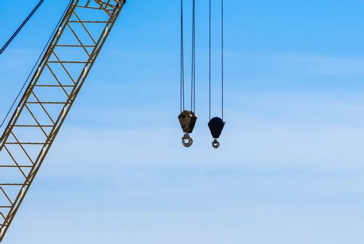 Pair of industrial crane hoists on cables near truss