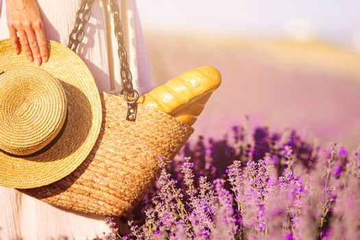Closeup straw bag and hat in lavender field