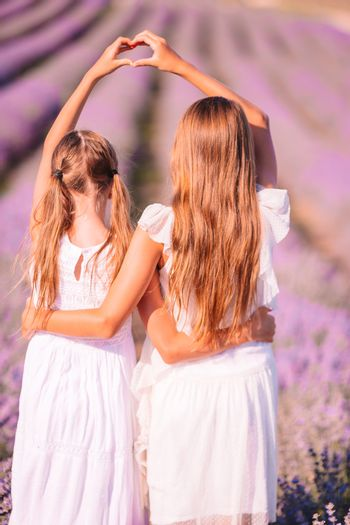 Girls in lavender flowers field at sunset in white dress