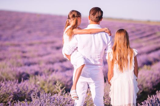 Happy father with his two little daughters on purple flower lavender field. Family vacation