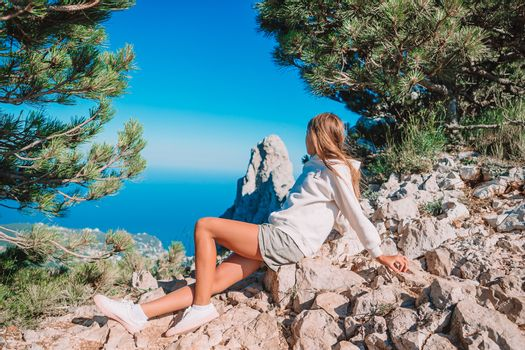 Little kid outdoor on edge of cliff seashore