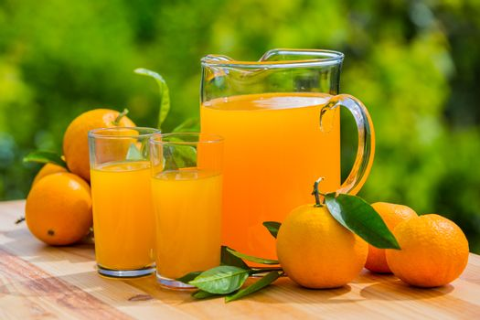 orange juice and oranges on table, outdoor