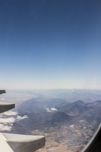 View from an airplane window at high altitude and turbines about South Africa. African Mountains.