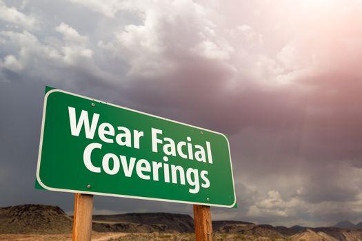Wear Facial Coverings Green Road Sign Against Ominous Stormy Cloudy Sky.