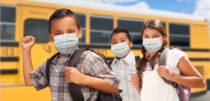 Hispanic Students Near School Bus Wearing Face Masks.