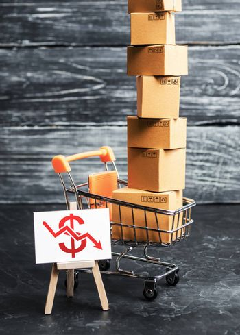 A shopping trolley loaded with boxes and an easel with a red dollar down arrow. Internet trade, online purchase. Drop in sales, economic recession. Retail of goods and services, search for new markets