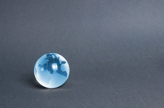 Blue glass planet globe on a gray background. Globalization and markets. Preservation of the environment and reduction of harmful effects on the ecosystem. International diplomacy. Foreign languages.