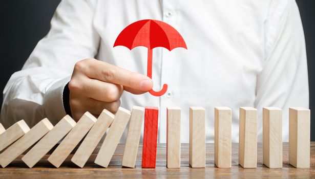 A businessman insures red dominoes and stops the collapse of the whole system. Insurance and risk management. Accurate forecasts and miscalculations. Financial support, subsidies and exemptions