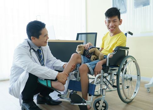 Asian doctors, adult men talking to patients with boy disabled in wheelchairs. Counseling and rehabilitation in disability in hospitals. Technology and modern medical science