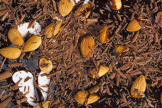 Almonds, grated and liquid chocolate on a white background
